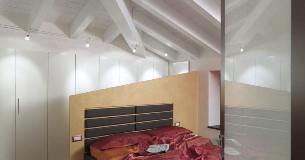 camera da letto con copriletto di raso rosso in mansarda